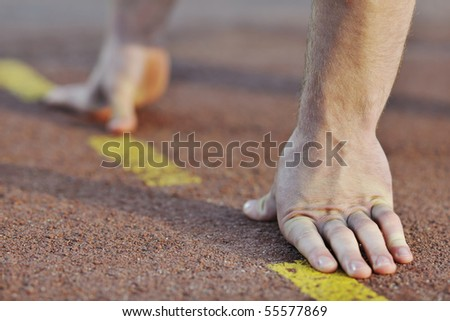 healthy young man at start line ready for run race and win - stock photo