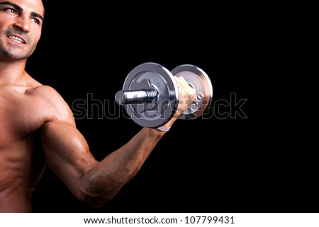 Healthy young man lifting weights on black background
