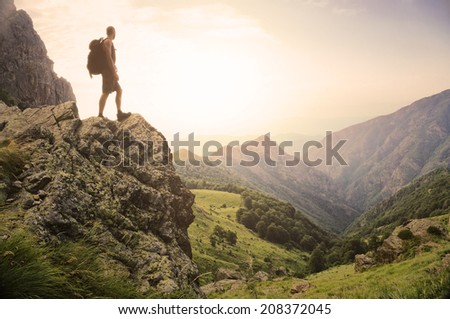 Healthy young man standing on top of a rock high in the mountains, enjoying the natural beauty in the morning light. - stock photo