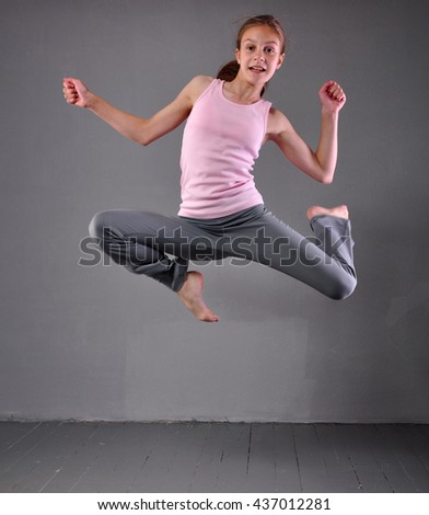 Healthy young muscular teenage girl dancer skipping jumping and dancing in grey studio. Child exercising. Sport healthy lifestyle concept. Sporty childhood. - stock photo