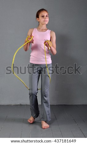 Healthy young muscular teenage girl skipping rope in studio. Child exercising with jumping high on grey background. Sport healthy lifestyle concept. Sporty childhood. - stock photo