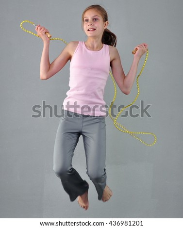 Healthy young muscular teenage girl skipping rope in studio. Child exercising with jumping on grey background. Sporty active childhood concept. - stock photo