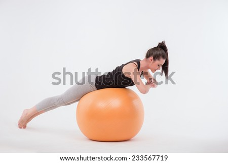 Healthy young sportswoman doing  the exercises doing stand on orange exercise ball  looking at it isolated on white background with copy place full length