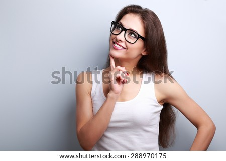 Healthy young thinking woman in glasses looking up on blue background with empty copy space