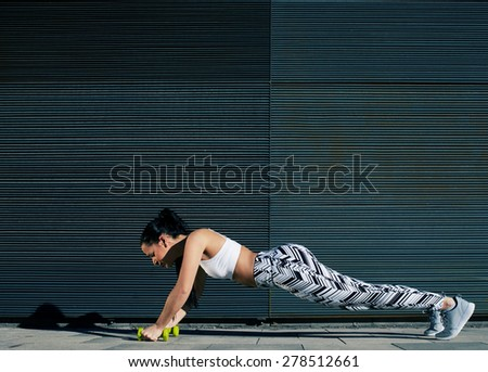 Healthy young woman doing press ups with dumbbells on black background outdoors, female in workout gear doing push-ups with some weights against wall with copy space for your text message, filter - stock photo