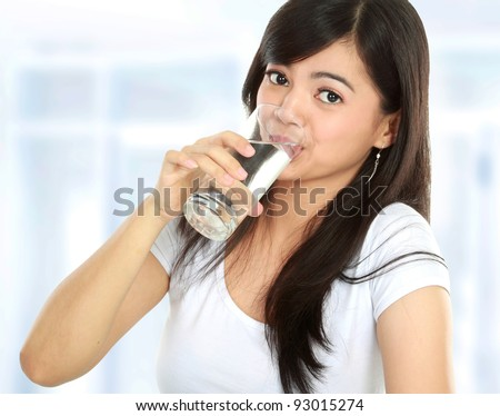 Healthy young woman drinking a glass of water - stock photo