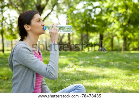 healthy young  woman drinking water in park - stock photo