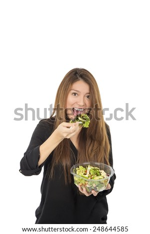 Healthy young woman eating a sale against a white background - stock photo