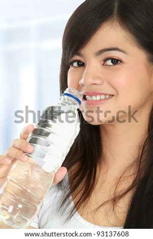 Healthy young woman holding a bottle of water and smiling to the camera - stock photo
