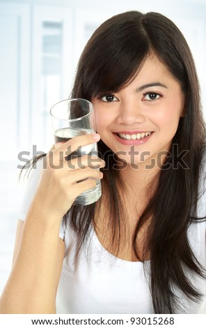 Healthy young woman holding a glass of water and smiling - stock photo