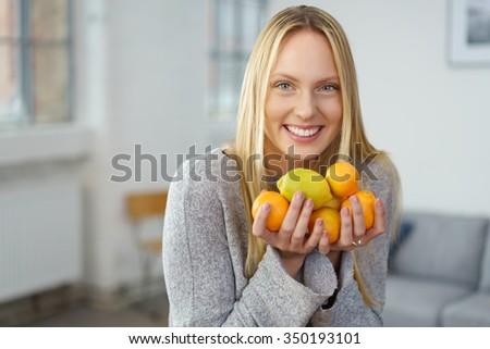 Healthy young woman holding assorted fresh citrus fruit as she smiles happily at the camera while standing in her living room at home in a healthy lifestyle and diet concept - stock photo