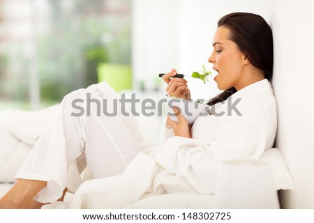 healthy young woman in bed eating fresh green salad - stock photo