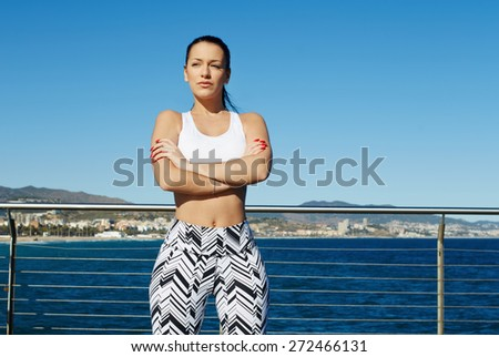 Healthy young woman in sports clothing with her arms crossed standing on sky background outdoors,charming female runner taking break while standing on wooden jetty of beautiful Mediterranean coastline - stock photo