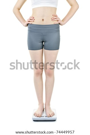 Healthy young woman standing on bathroom scale isolated on white - stock photo