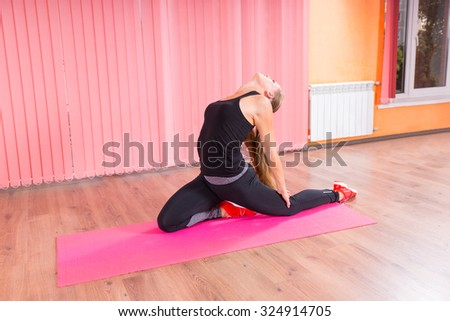 Healthy Young Woman Stretching her Back While Kneeling on a Pink Mat inside a Fitness Studio. - stock photo