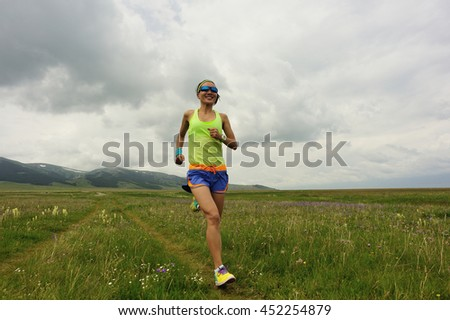 healthy young woman trail runner running on beautiful mountain trail