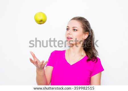 Healthy young woman wearing in pink shirt  throwing up green apple