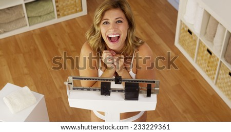 Healthy young woman weighing herself on scale - stock photo