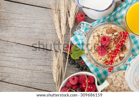 Healty breakfast with muesli, berries and orange juice. View from above on wooden table with copy space - stock photo