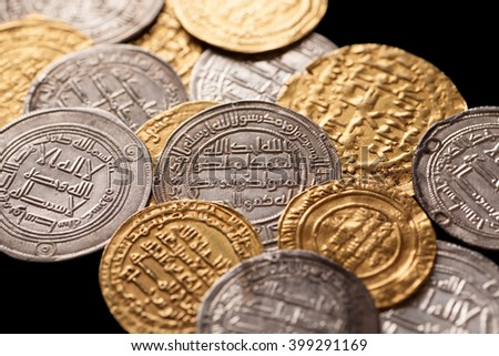 Heap of ancient islamic golden and silver coins with arabic letters isolated on black, closeup, selective focus - stock photo