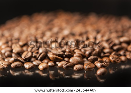 Heap of Aromatic Roasted Coffee Beans Placed over Black Background.Horizontal Image Composition - stock photo