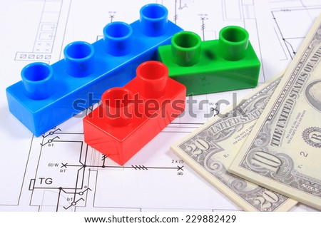 Heap of banknotes and plastic colorful building blocks lying on construction drawing of house, concept of building house - stock photo