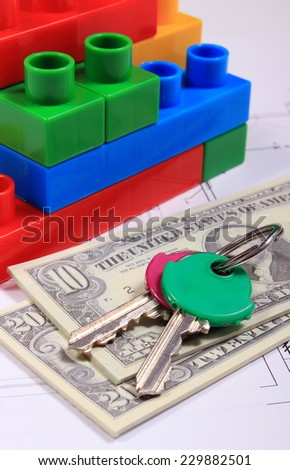 Heap of banknotes, home keys and wall of plastic colorful building blocks lying on construction drawing of house, concept of building house - stock photo