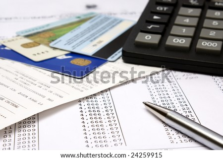 Heap of bills and checks, credit cards, the calculator, a ball pen. - stock photo