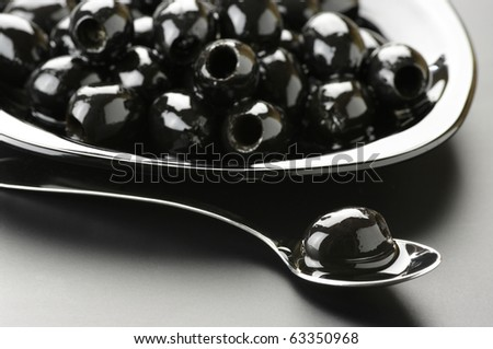 Heap of black olives in plate and olive in spoon on grey background.