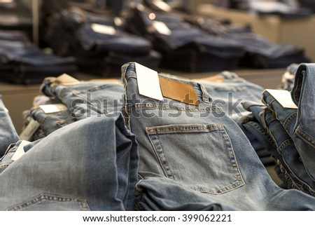 Heap of blue jeans for sale in store - stock photo