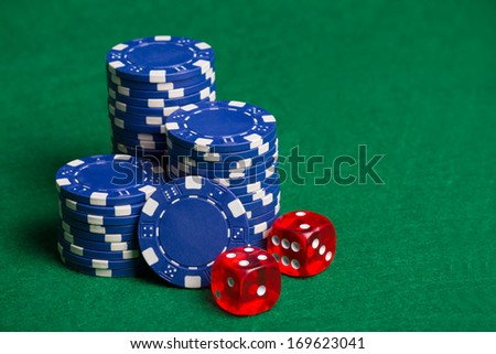 heap of blue poker chips and red cubes on the green table - stock photo