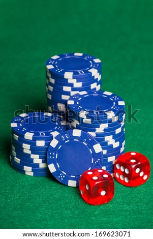 heap of blue poker chips and two cubes on the green table - stock photo