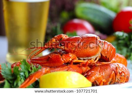 Heap of boiled crayfish, glass of beer and garnish (closeup, selective focus) - stock photo