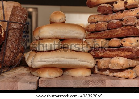 Heap of Bread Rolls Assortment and French Loaf on Wooden Board