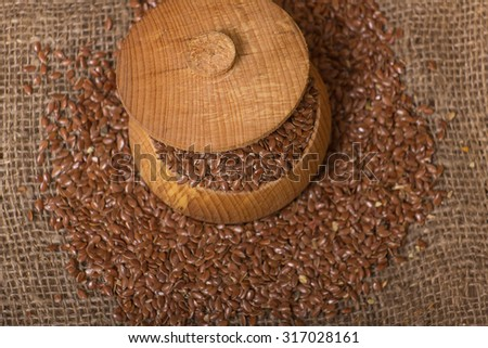 Heap of brown linseed, flax seeds on wooden background, concept for healthy nutrition - stock photo
