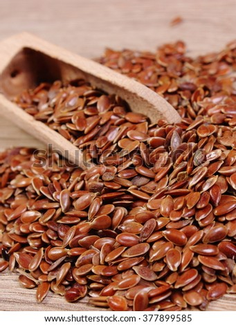 Heap of brown linseed, flax seeds with wooden spoon on wooden background, concept for healthy nutrition