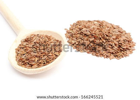 Heap of brown linseed with wooden spoon. Isolated on white background