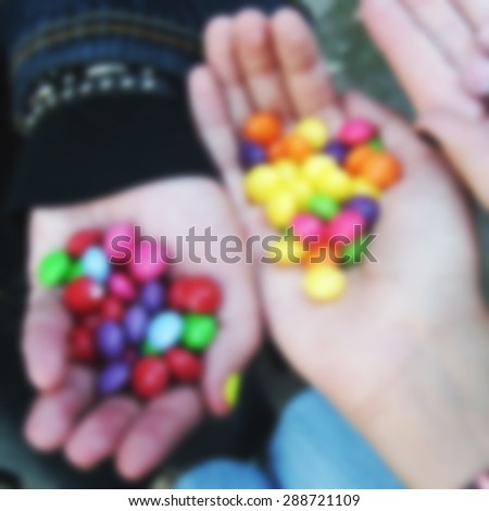 Heap of candies in hands photo blurred background - stock photo