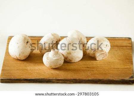 Heap of Champignons Mushroom on wooden background, selective focus - stock photo