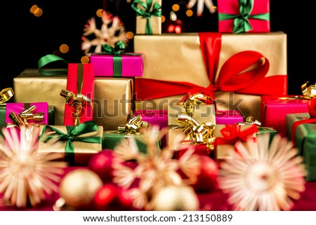 Heap of Christmas gifts in mainly golden and red colors. Blurred baubles and stars on red blanket in front. Bokeh effect against pitch black background. Shallow depth of field. - stock photo