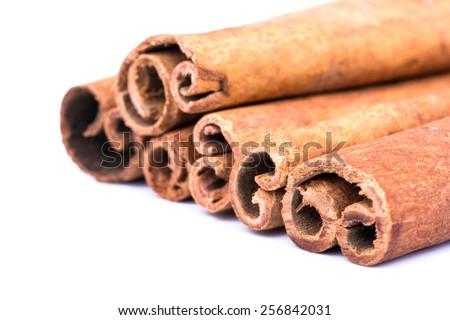 Heap of cinnamon sticks on a white background closeup - stock photo