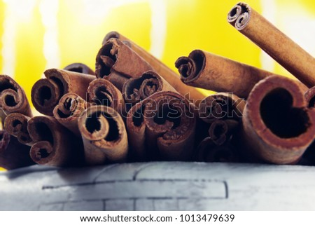 heap of cinnamon sticks on a wooden white foreground with bright yellow backlight on a background