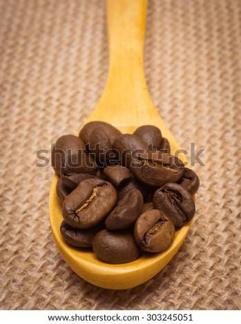 Heap of coffee beans on wooden spoon lying on jute burlap, coffee grains - stock photo