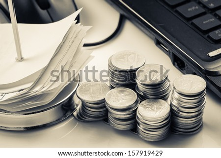 Heap of coins with receipts and laptop - stock photo