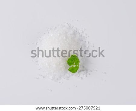 heap of crystal sea salt with piece of parsley - stock photo
