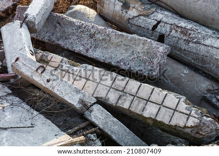 Heap of damaged concrete blocks, piles and pipes. - stock photo