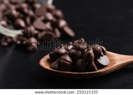 heap of dark chocolate chip in wooden spoon  - stock photo