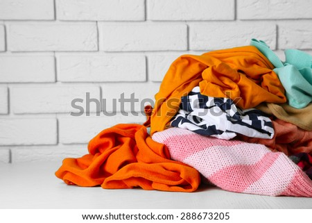 Heap of different clothes on wooden table, on bricks wall background
