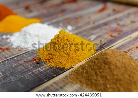 Heap of different dry spices on a wooden background. Various spices selection. Closeup
