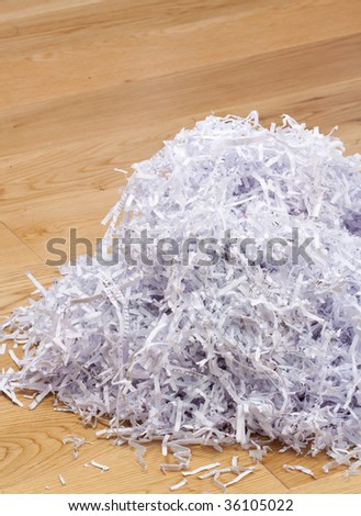 Heap of documents shredded for security purposes on the floor - stock photo